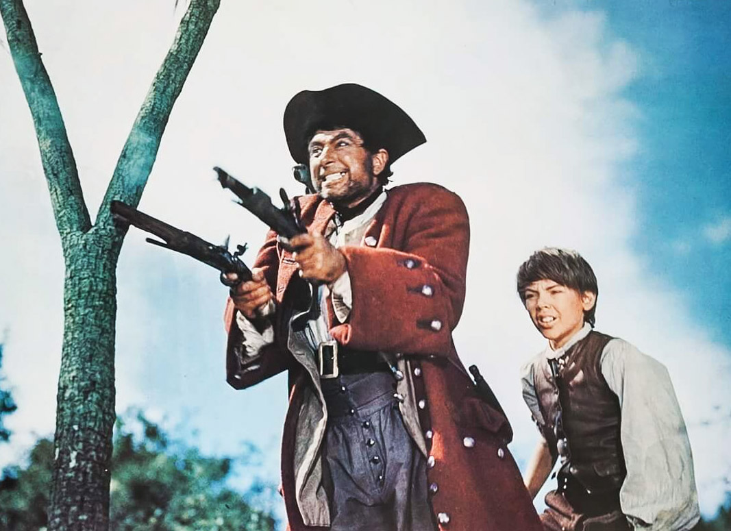 A picutre of an older man dressed like a pirate holding two pistols and a young boy next to him