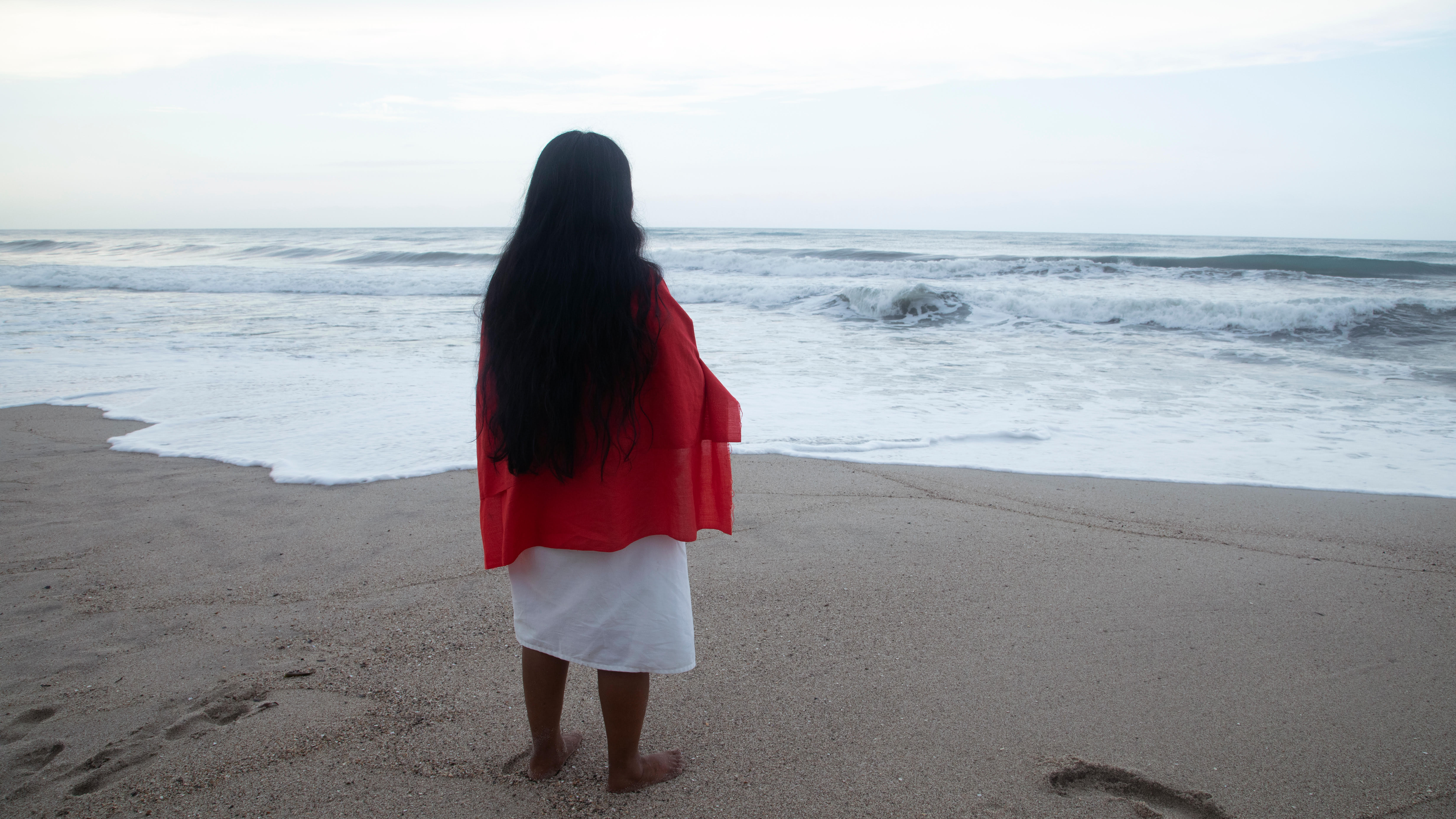 A person in a red shawl and white dress stands at the edge of the water on a beach with their back to the camera
